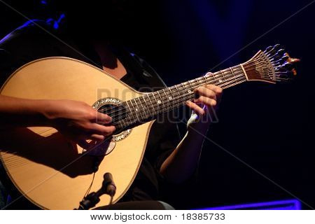 """fado"" - performer playing a tradicional portuguese guitar"