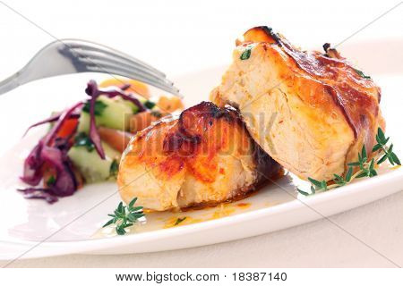 two pieces of roast chicken with bacon and salad isolated