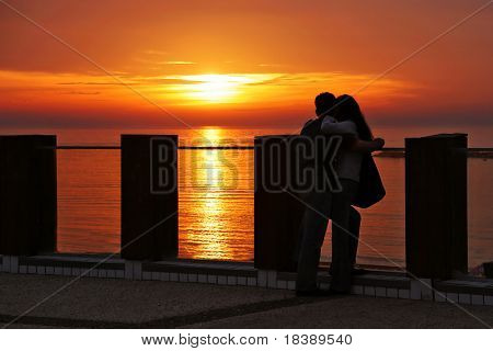 Silhouette of young couple standing on promenade and looking at sunset on Mediterranean Sea in Tel Aviv, Israel.