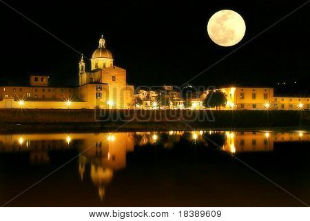 Night view at old church on Arno river and full moon at the black sky in Florence, Italy.