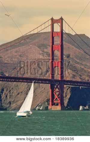 White yacht glides on water of San Francisco bay in front of Golden Gate Bridge.