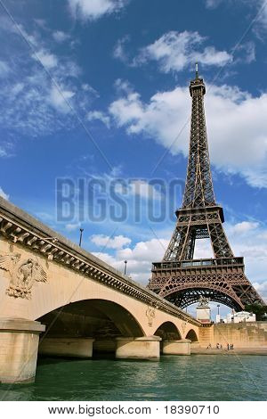 Vertical oriented photo of Eiffel Tower and fragment of bridge over the Seine River in Paris, France.