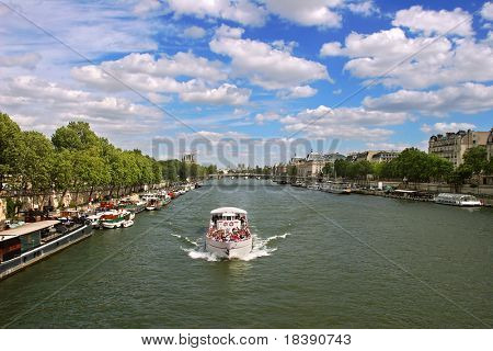 Touristic ship on Seine river under the beautiful cloudy sky in Paris, France.