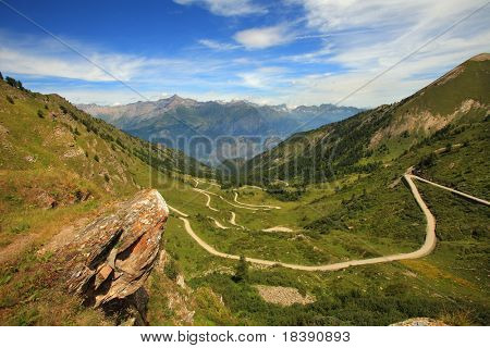 View on unpaved road running through the valley in Alps, Italy.