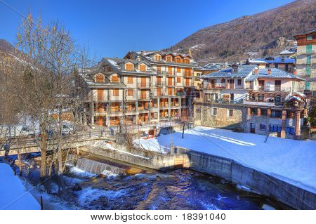 Hotel building and residential houses in snowy Limone Piemonte - popular touristic resort in northern Italy.
