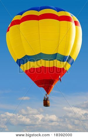 colorful hot air balloon above the clouds with clear blue sky background