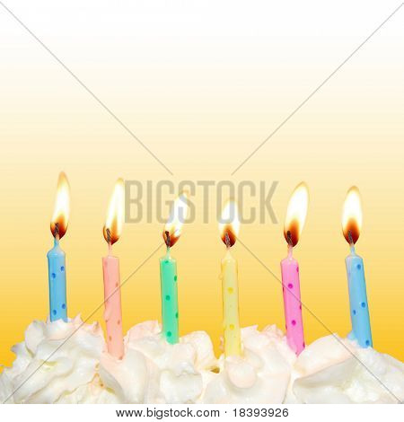 Colorful birthday candles on cake with whipped cream and yellow square background