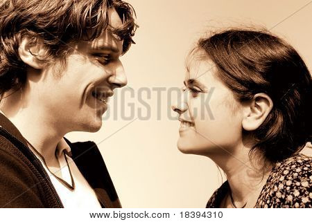 Young couple in their twenties smiling at each other in sepia color