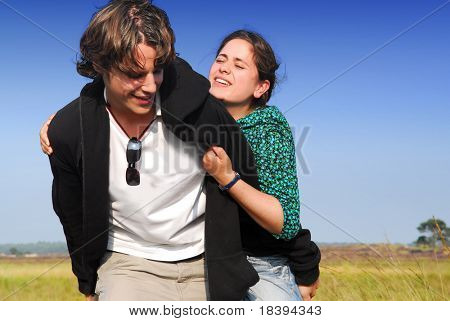 Playful young couple in their twenties with background of heath and lake, girl holding on to her boyfriend