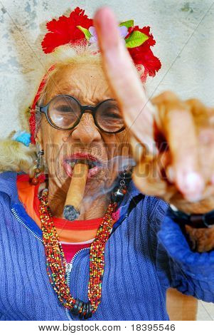 HAVANA â?? CIRCA DECEMBER 2008: An eccentric old Cuban lady smokes cigar and points finger circa December 2008 in Havana, Cuba.