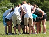 stock photo of huddle  - Flag football sports huddle during strategy session - JPG