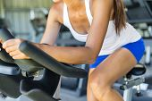 Woman doing HIIT cardio workout in indoors gym bike. Woman cyclist working out biking interval train poster
