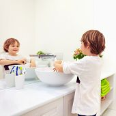 Cute Kid Washing Hand Under Tap Water In Bathroom poster