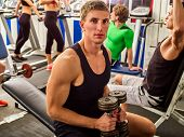 Friends in gym workout with fitness equipment. Man holding dumbbell workout at gym. Group people wor poster
