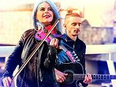 Playing viola woman and man perform music on violin and guitar in city outdoor. Girl with blue hairs poster