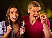 Couple eating in fast food restaurant. Man and woman eat slice pizza with knife and fork . Friends h poster
