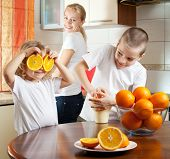 stock photo of healthy eating girl  - Happy mother with children squeezed orange juice - JPG