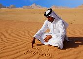picture of arab man  - Traditional arabic man writing in the sand in Wadi Rum desert - JPG