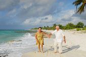 Active senior couple walking on the beach, getting wet, enjoying retirement on tropical destination: