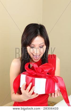 Asian Woman Holding a Gift Package Wrapped With Ribbon