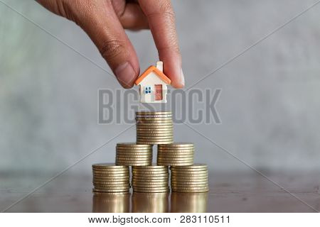 poster of Men's Hand Is Planning Savings Money Of Coins To Buy A Home, Concept For Property Ladder, Mortgage A