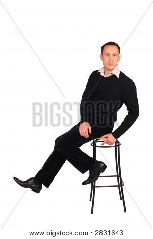 Young Man In Black Sits On Stool