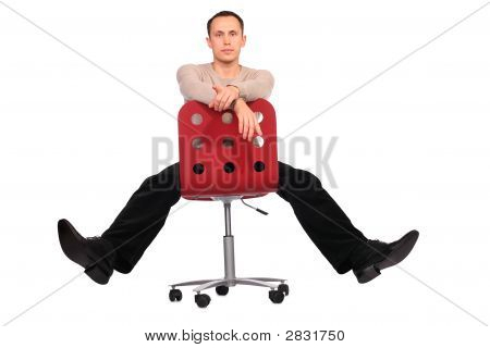 Young Man Sits On Red Chair Spread Legs