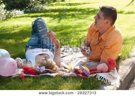 Happy Young Couple Having A Picnic And Making Bubbles