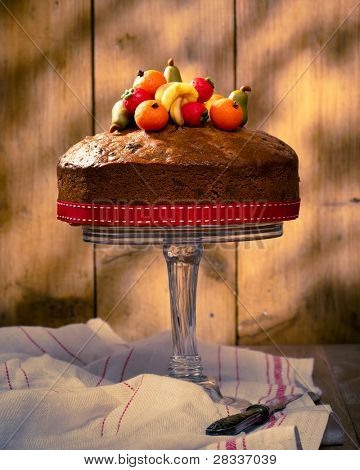 Rich fruit cake decorated with marzipan fruits with vintage feeling