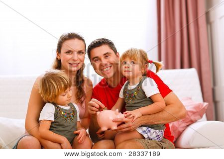 Family Portrait Where Father Putting Coin To Piggy Bank