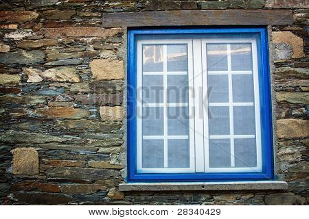 Ancient blue window on a wall made of schist