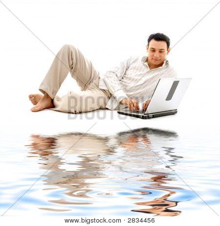 Entspannter Mann mit Laptop auf weißem Sand