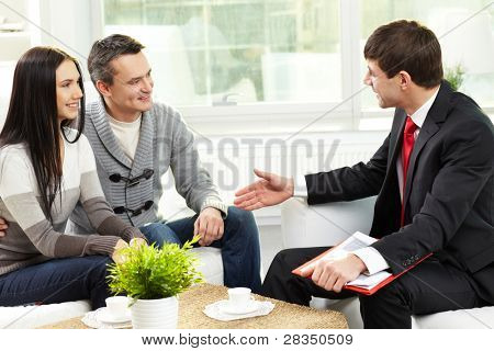 Portrait of modern couple listening to manager explanation about conditions of mortgage