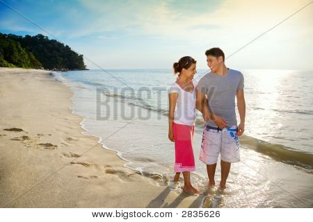 Happy Couple Walking Along The Beach