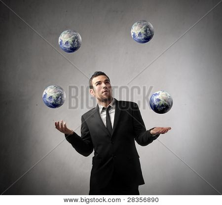 Young businessman juggling with some earth planets