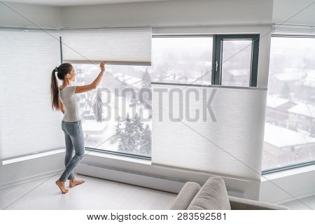 poster of Woman opening home curtains in urban condo. Modern top down bottom up privacy cellular shades on apa