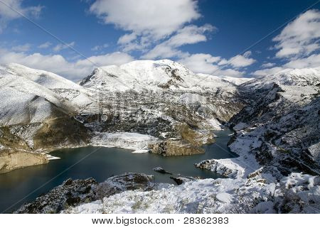 Landscape reservoir covered with snow under blue sky