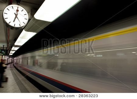 Blurred train at station with clock