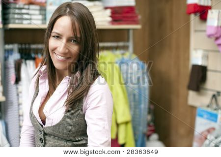 Smiling young shop assistant staring at camera