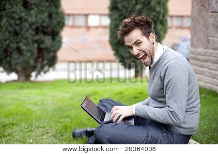 Stressed businessman portrait using laptop in park