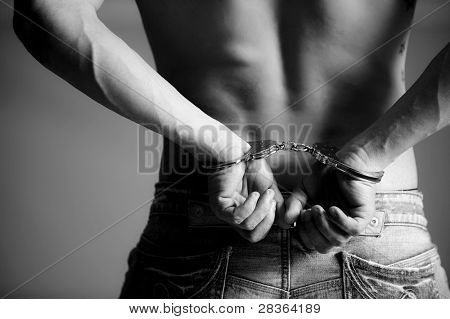 Closeup of man with handscuff and jeans.