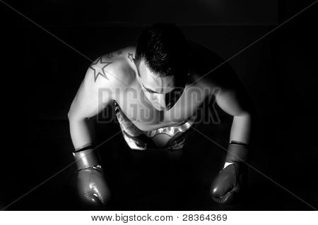 Topless male model performs pushup on floor with boxing gloves