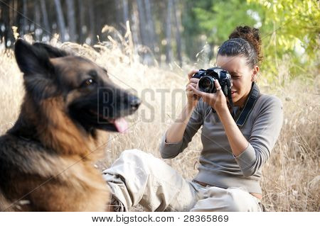 Young photographer taking a photo of her dog