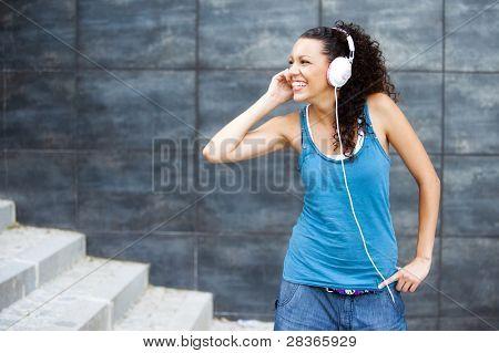 Jovem mulher esportiva feliz em ouvir música de fundo urbano