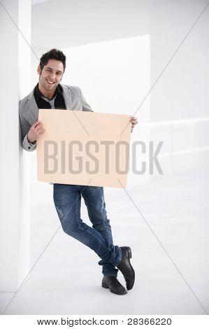 Atraente jovem, urbana e moderna fundo segurando uma placa em branco