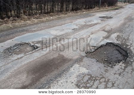 Damaged asphalt pavement road with potholes caused by freeze and thaw cycle during winter.