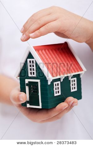 Protecting your home - child hands shielding house
