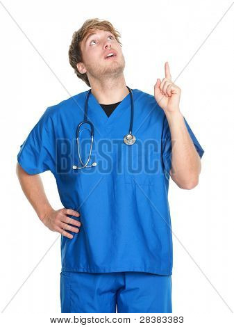 nurse or doctor pointing and looking up. Man wearing medical scrubs and stethoscope. Young caucasian male medical professional in his isolated on white background.