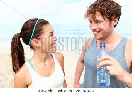 Fitness couple on beach talking relaxing and smiling happy after running training. Multiracial couple: Asian woman and Caucasian man drinking water
