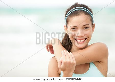 Fitness woman exercising smiling happy stretching out doing workout on beach. Beautiful mixed race Asian Caucasian female fitness model portrait.